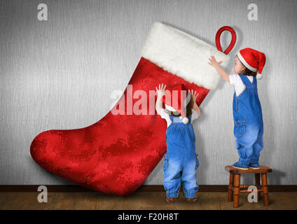 Little twins dressed Santa hat, hangs big Christmas stocking for gifts, xmas concept - Stock Photo