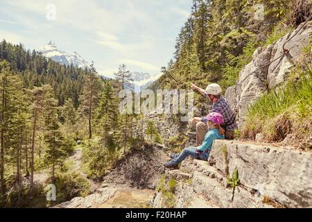 Father and child enjoying view on hill, Ehrwald, Tyrol, Austria - Stock Photo