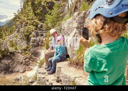 Father and children taking photograph on hill, Ehrwald, Tyrol, Austria - Stock Photo