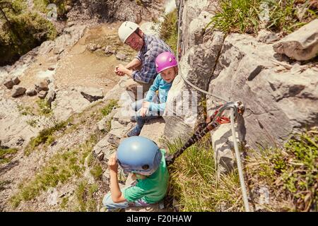 Father and children enjoying view on rocks, Ehrwald, Tyrol, Austria - Stock Photo
