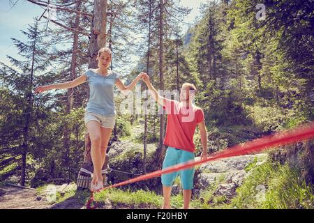 Woman balancing on rope with help from man, Ehrwald, Tyrol, Austria - Stock Photo