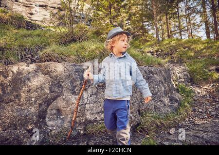One young boy, holding stick, exploring forest - Stock Photo