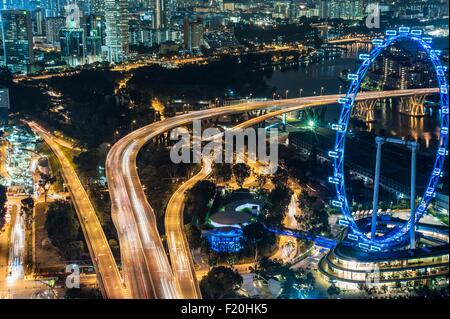 Aerial of highway and The Flyer at night, Singapore - Stock Photo