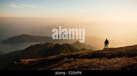 Rear view of hiker hiking on Lantau Peak, Lantau Island, Hong Kong, China - Stock Photo