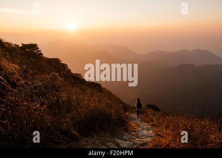 Rear view of hiker hiking along trail on Lantau Peak, Lantau Island, Hong Kong, China - Stock Photo