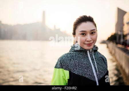 Portrait of young woman wearing tracksuit top in front of water smiling