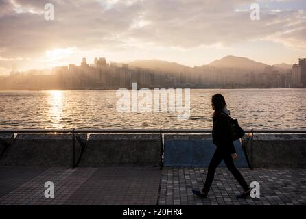 Side view of young woman walking past water, Hong Kong, China - Stock Photo