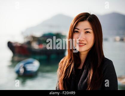 Portrait of mid adult woman in front of boats on water, looking at camera smiling - Stock Photo