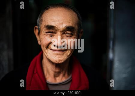 Portrait of senior man wearing red scarf around neck looking at camera smiling - Stock Photo