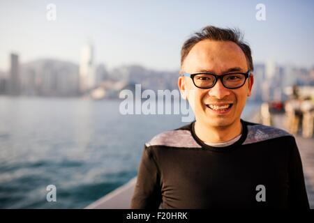 Portrait of mid adult man wearing glasses in front of water, looking at camera smiling - Stock Photo