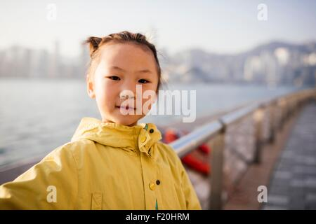 Portrait of young girl wearing yellow coat in front of water looking at camera - Stock Photo