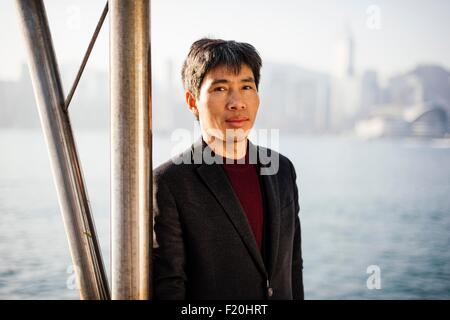 Portrait of mature man wearing suit jacket leaning against pole in front of water, looking at camera - Stock Photo