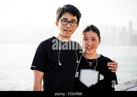 Portrait of young man with arm around young woman, wearing earphones, looking at camera smiling - Stock Photo