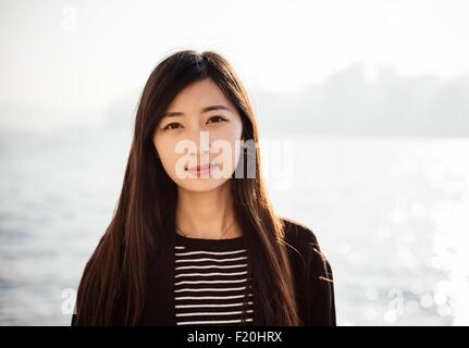 Portrait of young woman with long brunette hair wearing striped top looking at camera - Stock Photo
