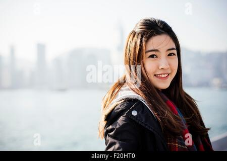 Portrait of young woman wearing checked scarf and leather jacket, looking at camera - Stock Photo