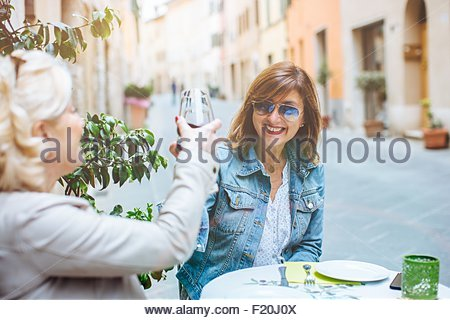 Two mature female friends making red wine toast, Tuscany, Italy - Stock Photo