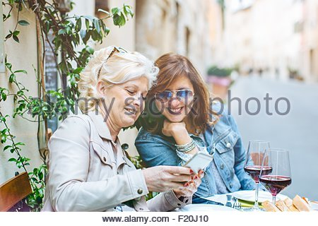 Two mature female friends looking at smartphone at sidewalk cafe, Tuscany, Italy - Stock Photo