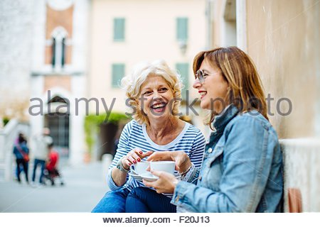 Two mature female friends talking and drinking coffee at sidewalk cafe, Tuscany, Italy - Stock Photo