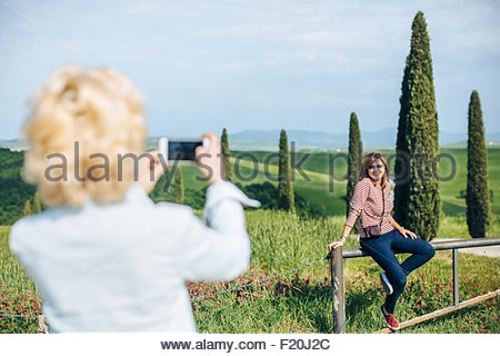 Two mature female friends taking smartphone photograph in landscape, Tuscany, Italy - Stock Photo