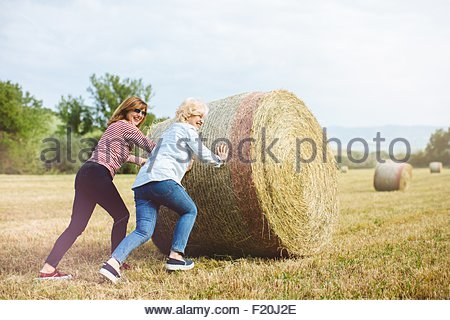 Two mature female friends pretending to push straw bale, Tuscany, Italy - Stock Photo