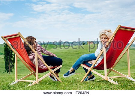Portrait of two mature female friends sitting on red deck chairs in landscape, Tuscany, Italy - Stock Photo