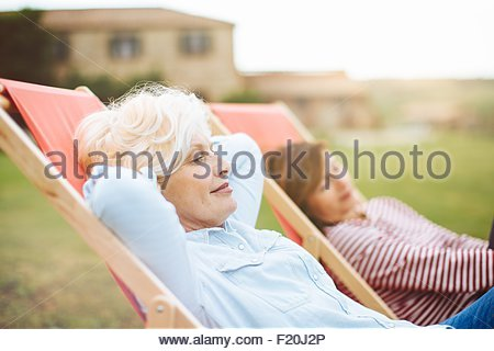 Two mature female friends sitting on deck chairs in front of villa, Tuscany, Italy - Stock Photo