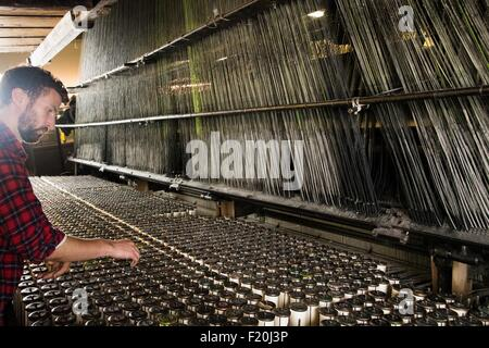 Male weaver using old weaving machine in textile mill - Stock Photo