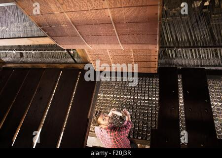 Overhead view of male weaver using old weaving machine in textile mill - Stock Photo