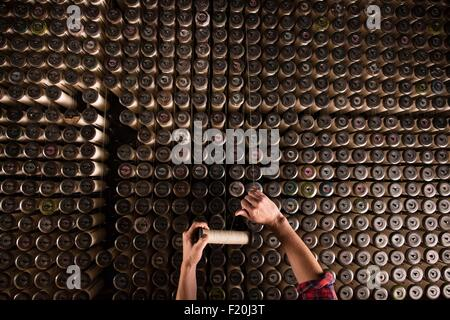 Overhead view of male weavers hands using old weaving machine in textile mill - Stock Photo