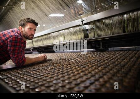 Male weaver monitoring old weaving machine in textile mill - Stock Photo