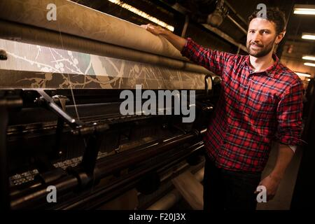 Portrait of male weaver next to old weaving machine in textile mill - Stock Photo