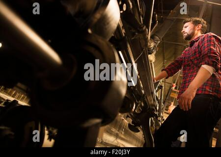 Low angle view of male weaver using old weaving machine in textile mill - Stock Photo