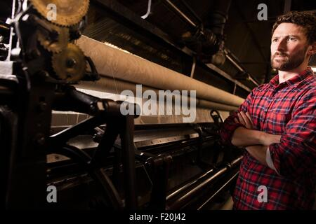 Portrait of young male weaver and old weaving machine in textile mill - Stock Photo