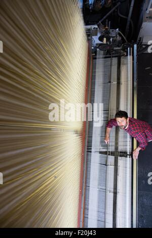 Overhead portrait of young male weaver and old weaving machine in textile mill - Stock Photo