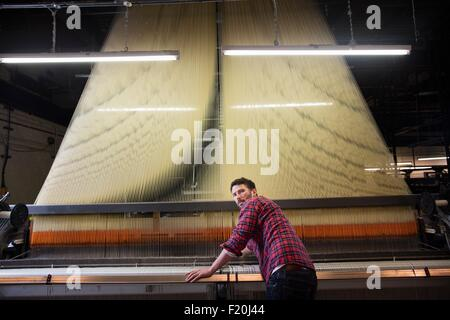 Overhead portrait of young male weaver at old weaving machine in textile mill - Stock Photo