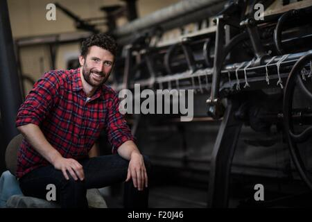 Portrait of young male weaver at old weaving machine in textile mill - Stock Photo