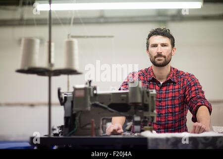 Portrait of male textile designer using sewing machine in old textile mill - Stock Photo