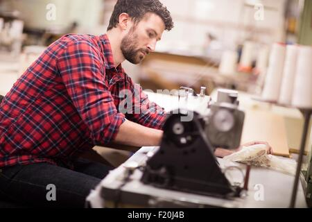 Male weaver using sewing machine in old textile mill - Stock Photo