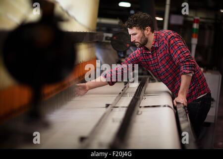Young male weaver using old weaving machine in textile mill - Stock Photo