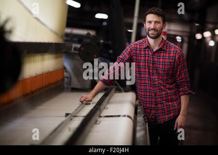 Portrait of young male weaver using old weaving machine in textile mill - Stock Photo