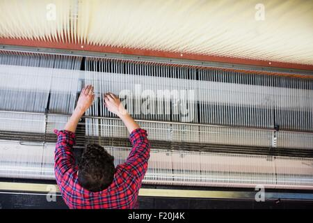 Overhead view of young male weaver adjusting threads on old weaving machine in textile mill - Stock Photo