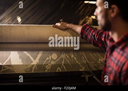 Young male weaver with lace roll on old weaving machine in textile mill - Stock Photo