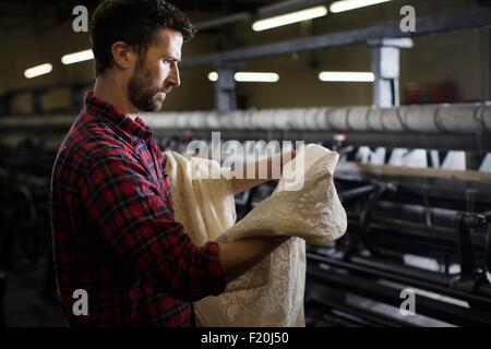 Portrait of male weaver examining lace from old weaving machine in textile mill - Stock Photo