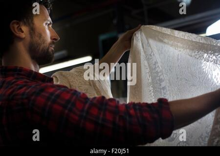 Portrait of male weaver examining lace product from old weaving machine in textile mill - Stock Photo