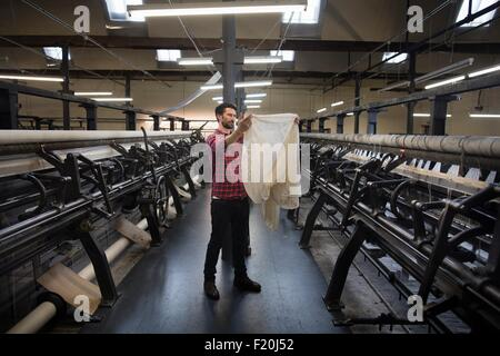 Portrait of male weaver examining cloth from old weaving machine in textile mill - Stock Photo