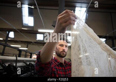 Portrait of male weaver examining lace cloth from old weaving machine in textile mill - Stock Photo