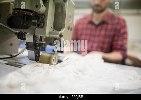 Male weaver sewing lace on sewing machine in old textile mill - Stock Photo