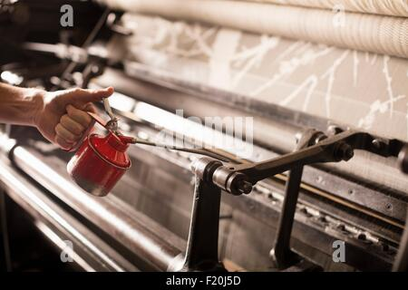 Hand of male weaver oiling old weaving machine in textile mill - Stock Photo