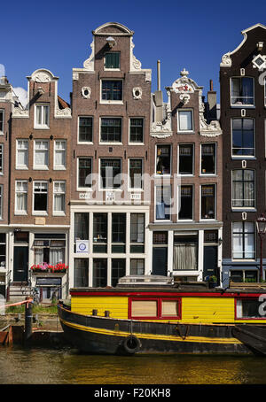 Netherlands, Noord Holland, Amsterdam, typical canal scene along the Herengracht with tall houses and boat sitting - Stock Photo
