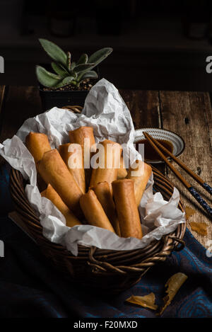 Traditional Asian Fried Spring Rolls with Dipping Sauce on Wooden Background - Stock Photo